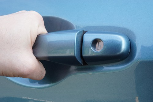 person pulling car door handle because they are locked out of the car
